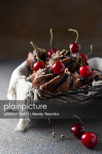 Basket of German minigugelhupf cakes with chocolate, brittle and cherries - p300m2155671 by Mandy Reschke