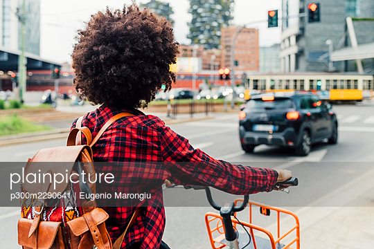 Young woman with backpack riding bicycle in city - p300m2290641 by Eugenio Marongiu
