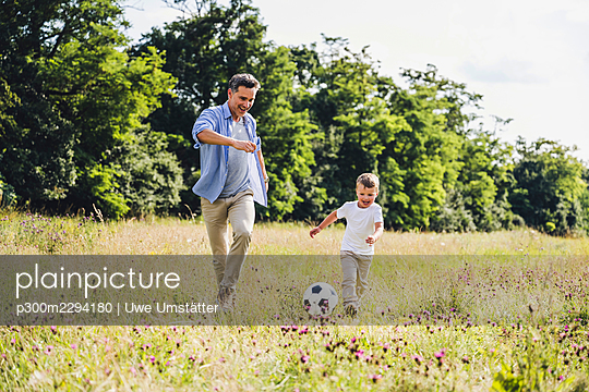 Cheerful father and son playing soccer on grass - p300m2294180 by Uwe Umstätter
