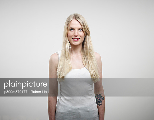 Portrait of young woman standing against white background, smiling - p300m879177 by Rainer Holz