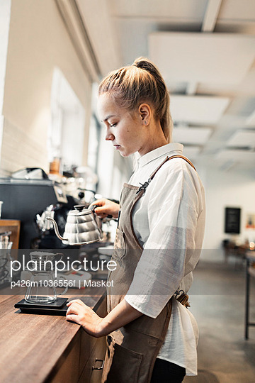 Side view of young female barista making coffee at counter - p426m1036556f by Maskot