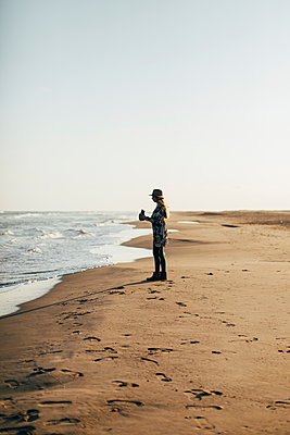 Woman holding camera enjoying at beach against clear sky during sunny day - p1166m1403160 by Cavan Images