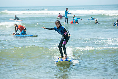 Full length of girl surfing on sea - p1166m2035064 by Cavan Images