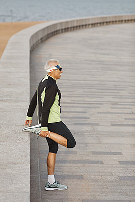 Man Doing Leg Stretching Exercise Side View - p1166m2147046 by Cavan Images