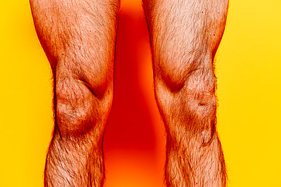 Hairy male legs in front of yellow background - p1267m2272507 by Jörg Meier