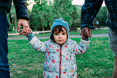 Portrait of fashionable little girl walking through a park on grandfather's and father's hands - p300m2041840 von Gemma Ferrando