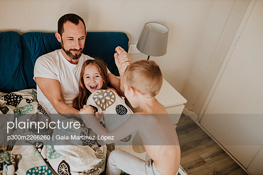 Playful children with father on bed at home - p300m2266260 by Gala Martínez López