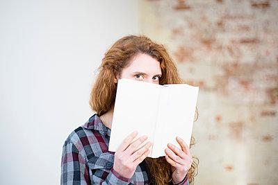 Junge Frau mit rötlichem Haar lesend, mit blanko Buchdeckel - p1325m1223155 von Antje Solveig
