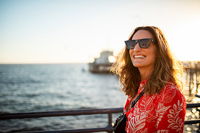 USA, California, Santa Monica, portrait of smiling woman at the waterfront - p300m2069712 by Daniel Waschnig Photography