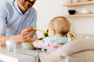 Father feeding baby girl in high chair - p300m2203035 by Sofie Delauw