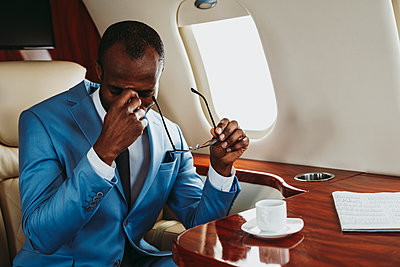 Worried male entrepreneur sitting in private jet - p300m2256380 by OneInchPunch
