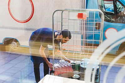 Young male owner carrying bottles from rack against food truck seen through restaurant window glass - p426m2046521 by Maskot