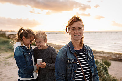Portrait of smiling mother with children at beach - p426m2205284 by Kentaroo Tryman