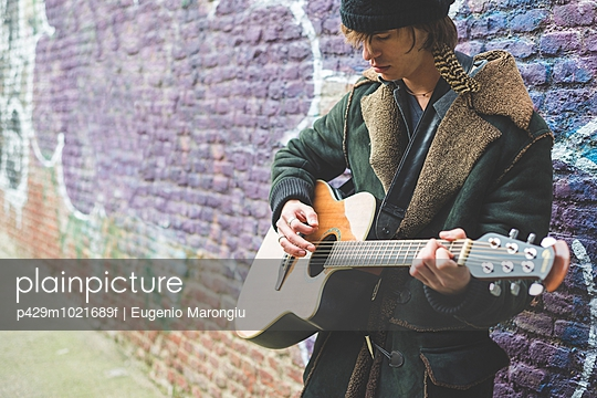Musician playing guitar by canal wall, Milan, Italy - p429m1021689f by Eugenio Marongiu