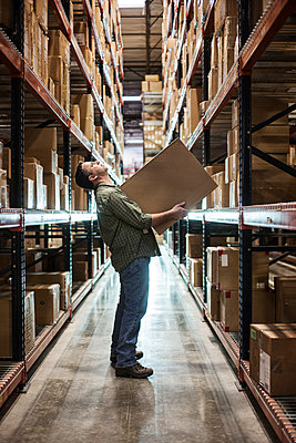 Caucasian male warehouse worker standing in an aisle, holding a box and checking inventory on stacks of cardboard boxes holding products on large racks in a large distribution warehouse - p1100m1575480 by Mint Images