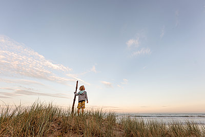 Young boy holding a stick watching the ocean - p1166m2129646 by Cavan Images