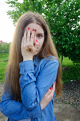 The girl covers her face with a palm on which butterflies sit - p1412m1575143 by Svetlana Shemeleva