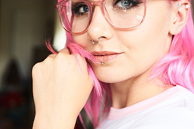 Portrait of young woman with pink hair, glasses and piercings - p300m1494764 by Ivan Gener Garcia