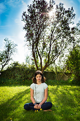 Girl sitting on meadow listening music with headphones - p300m1587372 von Larissa Veronesi