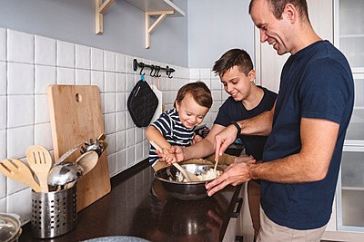Moskau, Russland. Ein lachender glücklicher Mann mit zwei Kinder bereit das Essen auf der Küche vor - p300m2276665 von Katharina und Ekaterina