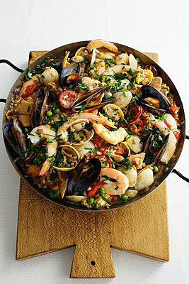 Pan of paella on wooden board - p429m696556 by Brett Stevens