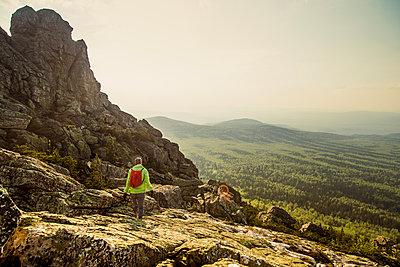 Caucasian hiker walking on rocky hillside in remote landscape - p555m1411148 by Aleksander Rubtsov