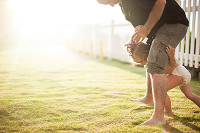 Father and son fooling around outdoors, young boy walking between father's legs - p924m1422657 by Sasha Gulish