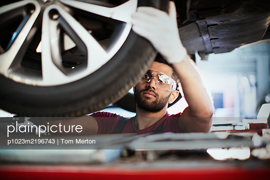 Male mechanic working under car, examining tire in auto repair shop - p1023m2196743 by Tom Merton