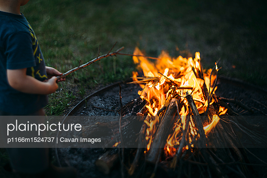 Midsection of boy holding stick while standing by fire pit - p1166m1524737 by Cavan Images
