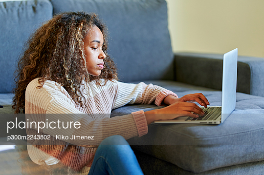 Young woman with curly hair using laptop in living room at home - p300m2243802 by Kiko Jimenez