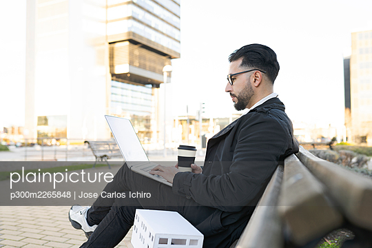 Male architect using laptop while sitting on bench in city - p300m2265848 by Jose Carlos Ichiro