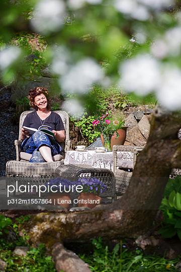 Smiling woman in garden - p312m1557864 by Lena Oritsland