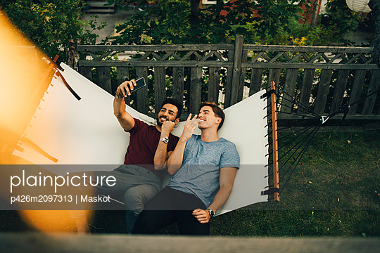 High angle view of smiling friends taking selfie on smart phone while resting in hammock at yard - p426m2097313 by Maskot