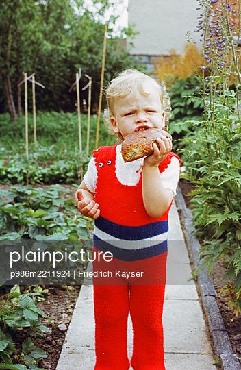 Kleiner Junge beißt in ein Brot - p986m2211924 von Friedrich Kayser