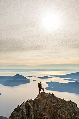 High angle view of carefree hiker with backpack standing on mountain against cloudy sky - p1166m1509603 by Cavan Images