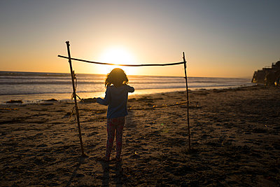 Young girl on beach at sunset - p1166m2087992 by Cavan Images