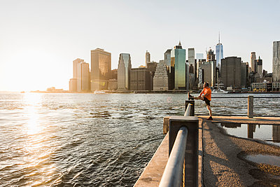 USA, Brooklyn, man doing stretching exercises in front of Manhattan skyline in the evening - p300m1205316 by Uwe Umstätter