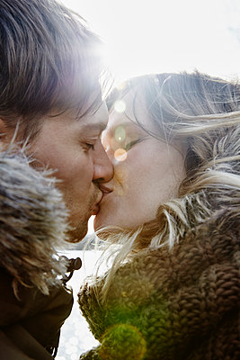Kissing young couple in winter at backlight - p300m2166235 by Annie Hall