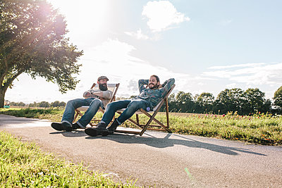 Two friends relaxing at the roadside - p586m1091087 by Kniel Synnatzschke