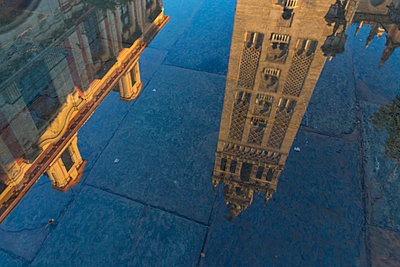 Reflection of the Giralda Bell Tower in a puddle, Seville, Andalusia, Spain - p871m2058016 by Oliver Wintzen
