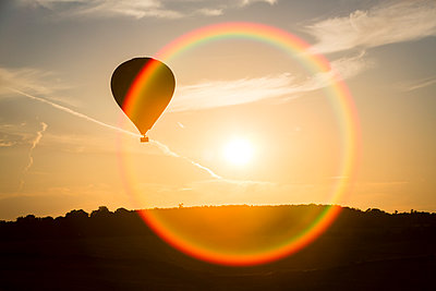 A hot air ballon flies past the setting sun - p1057m931350 by Stephen Shepherd