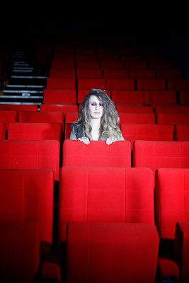 Blonde Frau sitzt in einem alten Kinosaal - p1105m2254501 von Virginie Plauchut