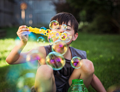 A young boy blowing bubbles outdoors on a summer day. - p1166m2138084 by Cavan Images
