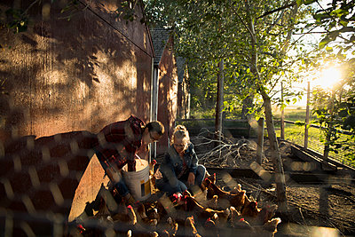 Mother and daughter farmers feeding chickens in chicken coop - p1192m1493190 by Hero Images