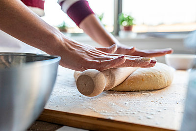 Woman rolling out dough on cutting board in kitchen at home - p300m2257407 by William Perugini