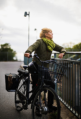 Young woman on bicycle - p312m2080730 by Pernille Tofte