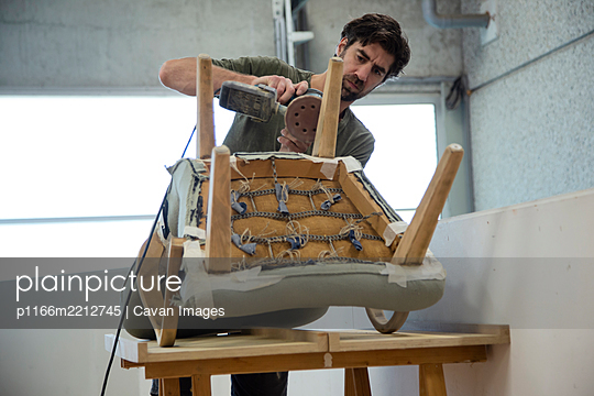 Low angle view of a man repairing and restoring an old chair - p1166m2212745 by Cavan Images