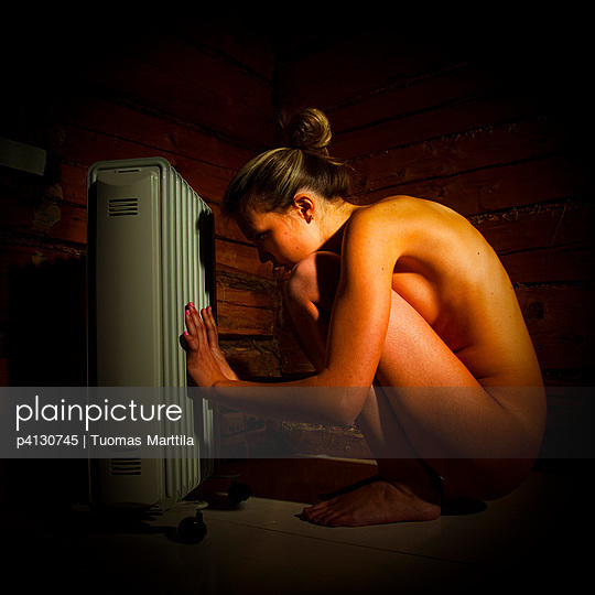 Woman sitting in front of a heater in a log house - p4130745 by Tuomas Marttila