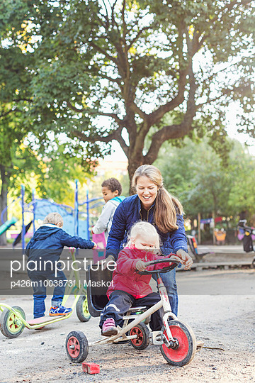 Happy teacher assisting girl to ride tricycle on playground