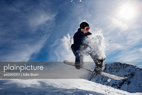 Male snowboarding on mountain, action shot